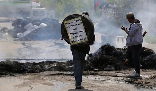 """Un abitante locale filorusso di Kramatorsk tiene in mano uno pneumatico con un cartello che dice in inglese e in russo: """"Putin non lasciare che ci uccidano!"""", 3 maggio 2014 (AP Photo/Max Vetrov)"""