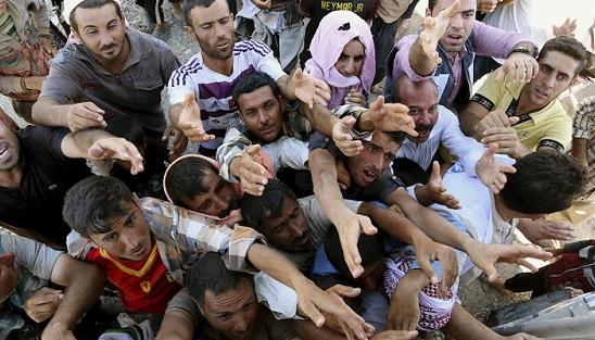 Profughi yazidi in fila per ricevere gli aiuti umanitari distribuiti dal personale ONU vicino al confine tra Siria e Iraq (AP Photo/ Khalid Mohammed)