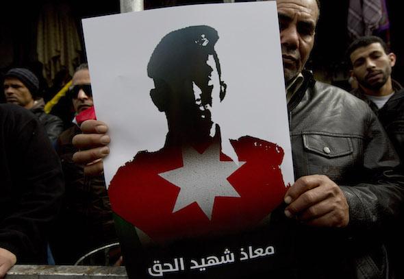 Un uomo regge un manifesto con una foto del pilota giordano ucciso, Muath al-Kaseasbeh, durante una marcia anti-ISIS ad Amman, in Giordania.